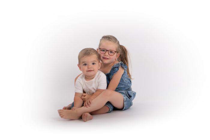 portfolio kinderen zus en broertje zittend op grond
