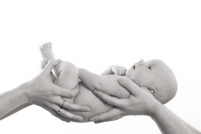 portfolio newborn jongetje close up ligt in handen van ouders