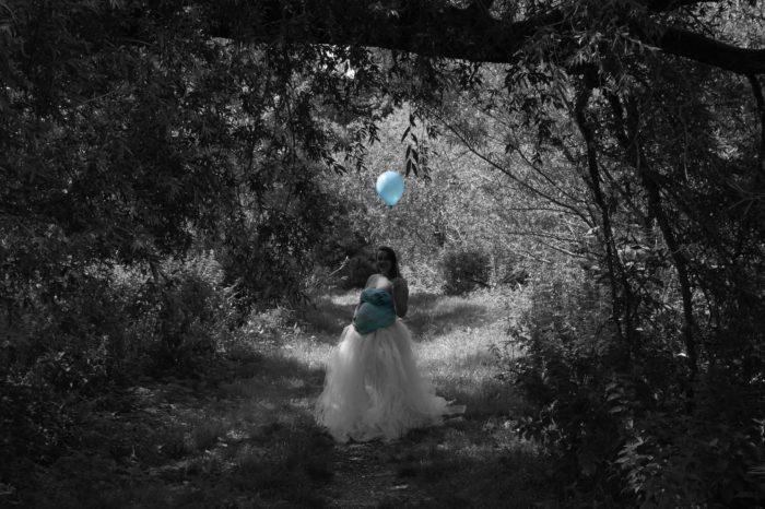 portfolio zwangerschap vrouw met blauwe top en blauwe ballon buiten